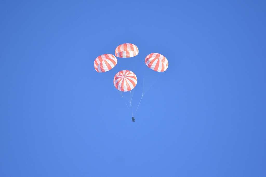 Accroché aux quatre parachutes, un simulateur de masse reproduit la descente d'une capsule Dragon habitée de retour d'orbite. © SpaceX