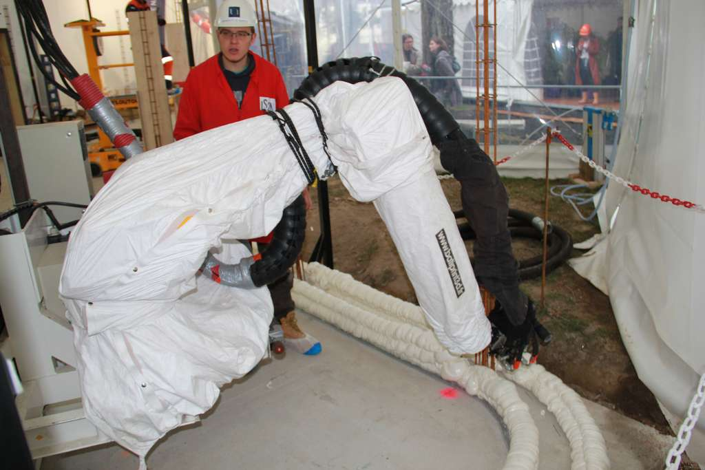 La machine, qui suit le plan informatisé, pose deux cordons de polyuréthane. Elle coulera ensuite, entre les deux, du béton. © DR