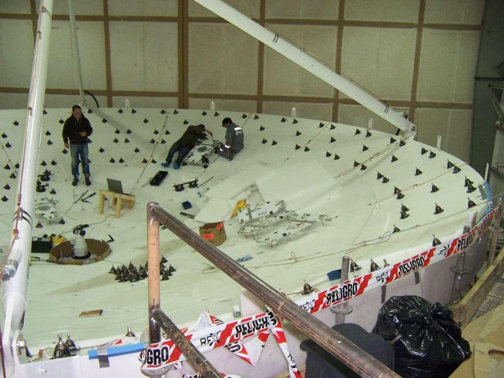 Travaux d'installation des panneaux de la parabole d'une antenne. © Thales Alenia Space