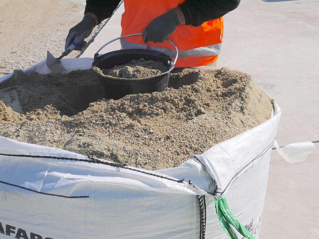 Pour doser le béton, le seau est plus pratique et précis que la pelle. © Lafarge