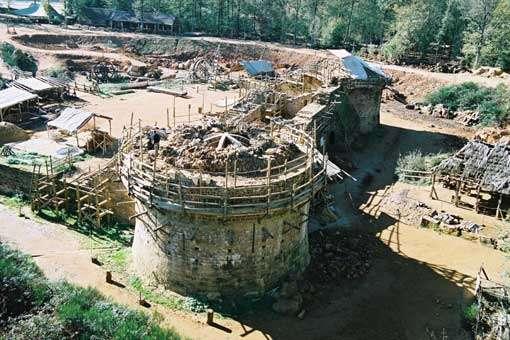 Vue nord-est de la tour maîtresse. En 2013, les travaux d'élévation du second étage se poursuivent. Terminée la tour maîtresse fera 30 mètres. Au pied de la tour, on aperçoit la cage à écureuil (engin de levage) qui permet de monter pierres et mortier sur la tour en construction. © Guedelon - Reproduction et utilisation interdites - Tous droits réservés