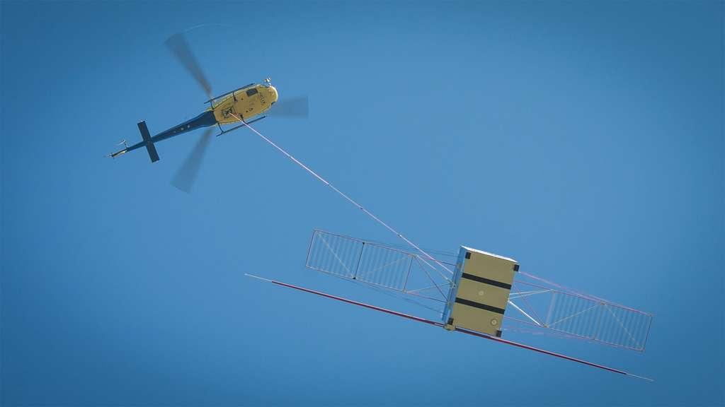 Essai du radar Rime installé sur la maquette de la sonde Juice. L'ensemble était suspendu à une corde en polyéthylène d'environ 120 mètres en dessous d'un hélicoptère évoluant à 320 mètres au-dessus du sol. © Airbus