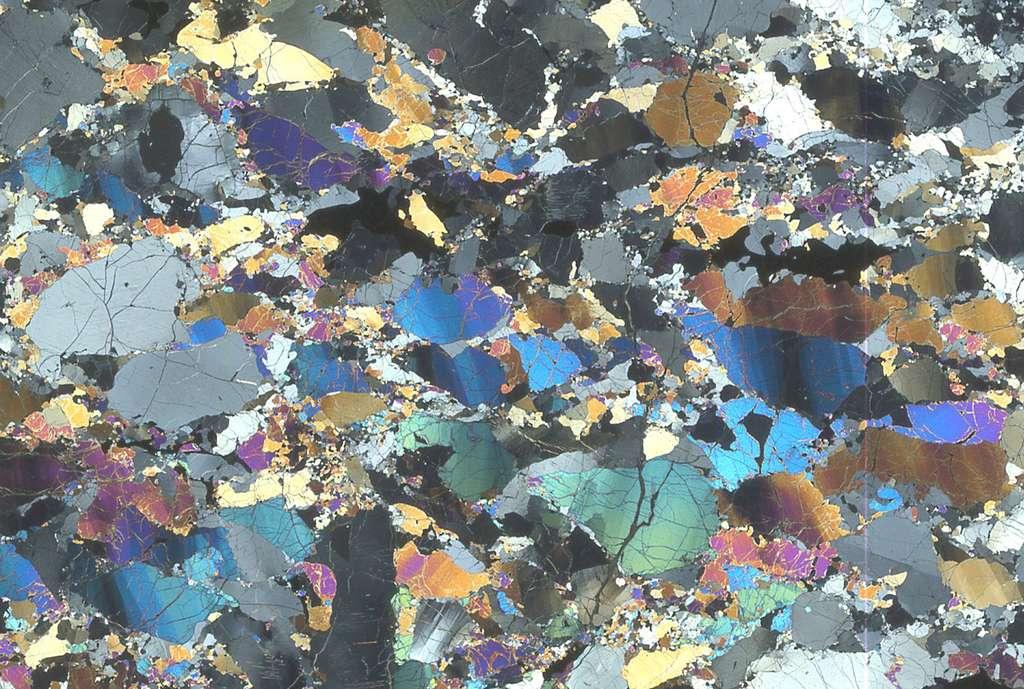 Sur cette lame mince de péridotite du Massif central, observée en LPA, on remarque les « bandes de pliage » dans les gros cristaux, et la recristallisation de ces derniers en éléments beaucoup plus fins. © Françoise Boudier