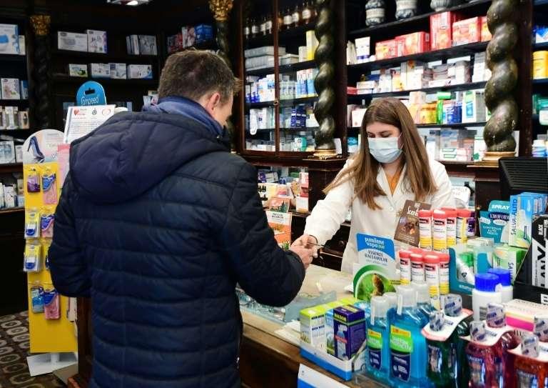 Une pharmacienne équipée d'un masque respiratoire sert un client le 22 février 2020 à Codogno, en Italie. © Miguel Medina, AFP