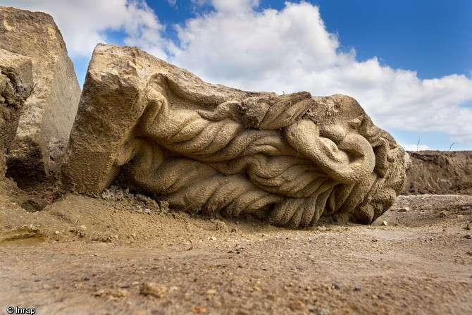 Fragment de statuaire monumentale ornant le haut de la façade du sanctuaire et figurant une tête mutilée, peut-être Apollon. © Denis Gliksman, Inrap