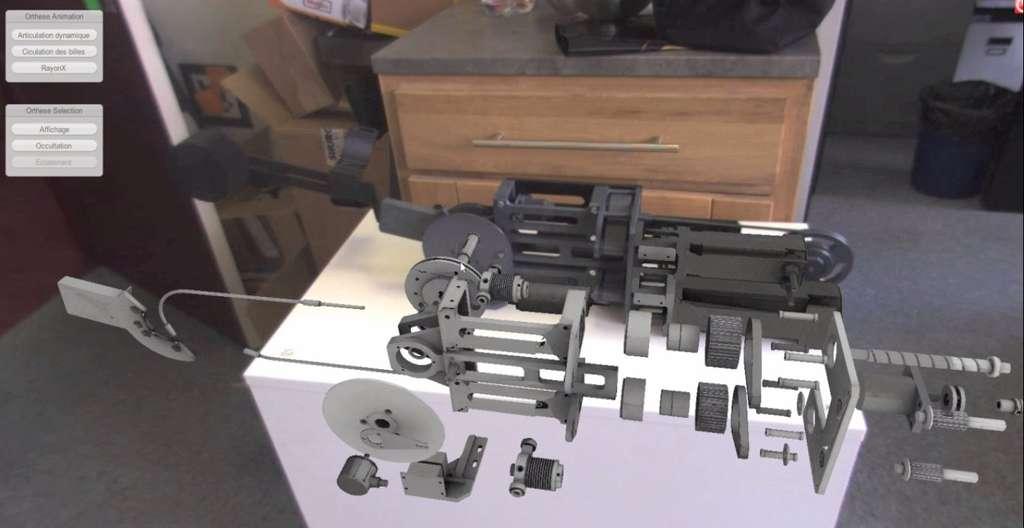 Un objet réel (en noir) observé à travers une tablette, via sa caméra dorsale et l'écran. Un logiciel l'a reconnu et plaqué sur lui un schéma enregistré en mémoire. L'utilisateur peut alors tourner autour de l'objet et afficher des informations, comme ici l'éclaté d'un mécanisme interne. © Futura-Sciences, Jean-Luc Goudet