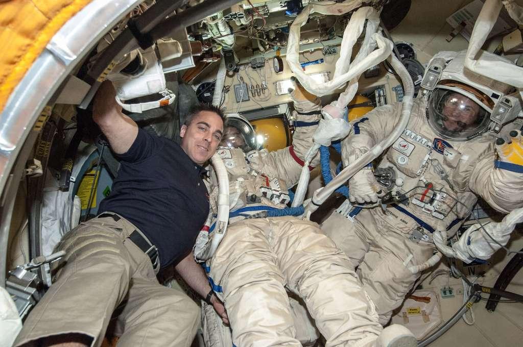 Les deux cosmonautes Pavel Vinogradov (au centre) et Roman Romanenko (à droite) se préparant à sortir dans l'espace. Leur combinaison est d'origine russe, mais le casque est fourni par la Nasa. © Nasa