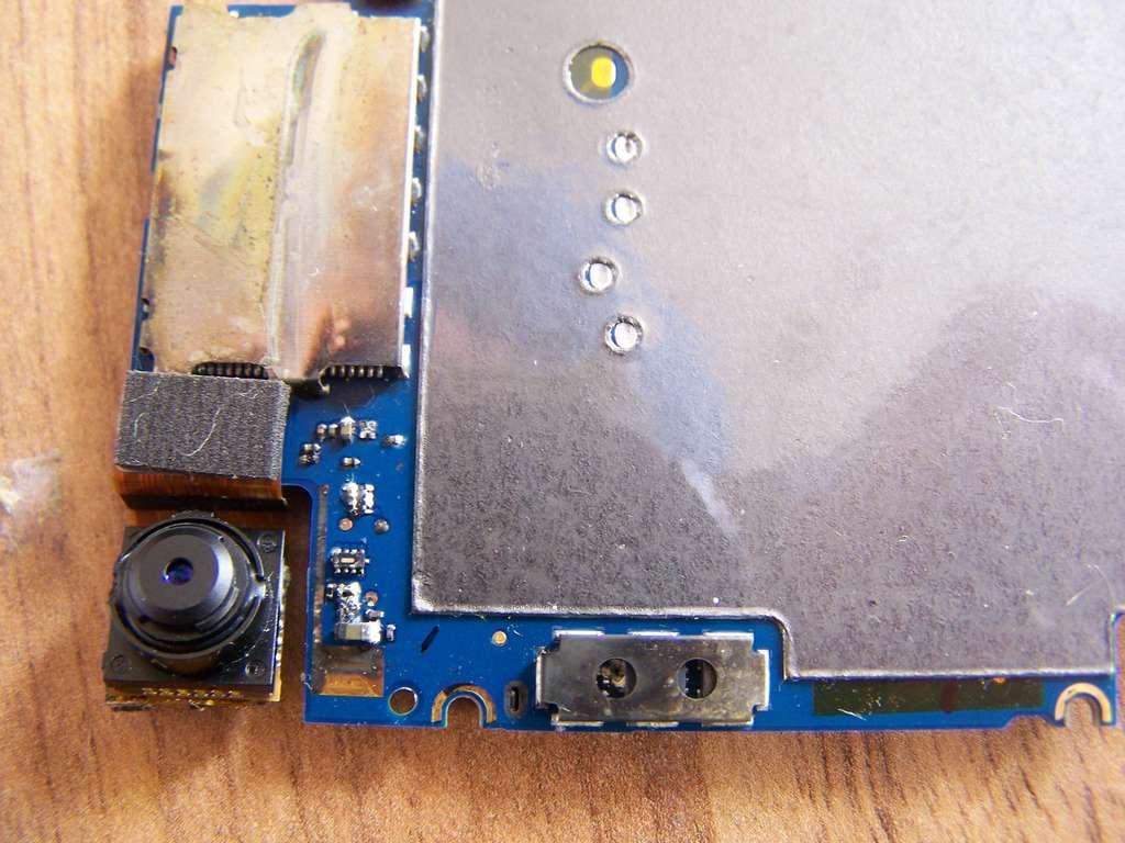 Sur cette image, on voit l'arrière de la carte mère qui a des traces de corrosion au niveau des contacts de la batterie. © iFixit CC by-nc-sa
