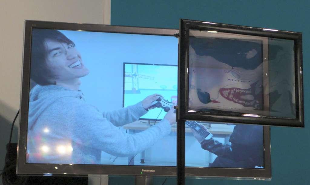 Derrière l'écran polarisant, qui pourrait être une lunette, une autre image apparaît, différente de celle affichée sur le téléviseur 3D. Ce système baptisé Familink, encore expérimental, pourrait avoir différents usages. Un film pourrait être vu en relief avec des lunettes et en 2D lorsqu'on les enlève. Un écran d'ordinateur pourrait afficher deux images, dont une cachée. Deux personnes pourraient regarder deux programmes de télévision différents. Etc. © Futura-Sciences, Jean-Luc Goudet