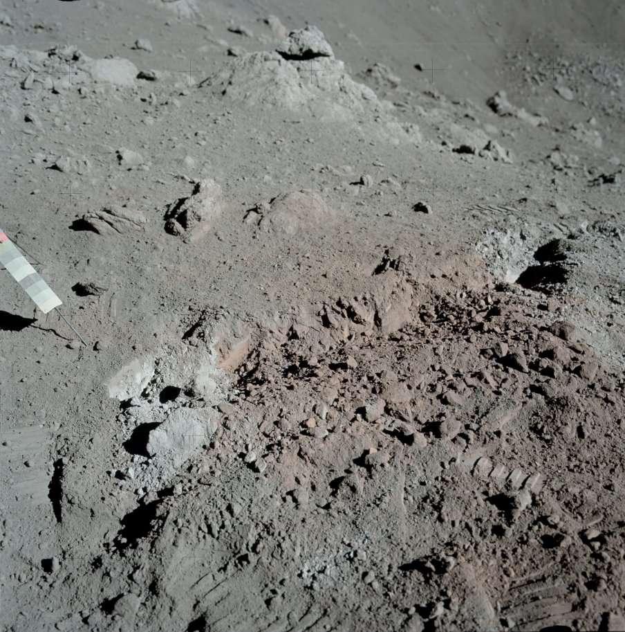 Le « sol orange » découvert par le géologue Harrison Schmitt lors de la mission Apollo 17 non loin du site d'alunissage de Taurus-Littrow. L'objet dont on voit une partie sur la gauche est un gnomon équipé d'une charte photométrique qui sert de référence pour interpréter les couleurs de l'image. © Nasa