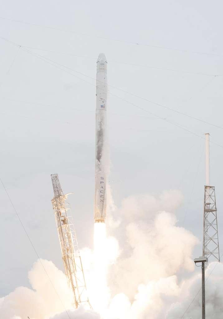 Le premier étage du lanceur Falcon 9 lors de son décollage (sur lequel est inscrit « SpaceX »). Sur ses flancs, les quatre pieds, repliés, de son système d'atterrissage. Pendant l'ascension du lanceur, ils n'ont pas d'effet négatif sur son comportement. Le lanceur a décollé de son pas de tir de Cap Canaveral en Floride vendredi 18 avril à 15 h 25 (19 h 25 TU). © Nasa, Kim Shiflett