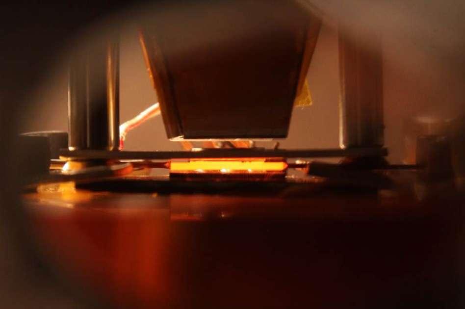 Dans cette image, l'absorbeur-émetteur imaginé au MIT est en plein fonctionnement. Il s'agit de la structure orange qui brille au centre de l'image, au-dessus de la cellule photovoltaïque. Notons que les tests ont été réalisés dans un environnement sous vide. © John Freidah