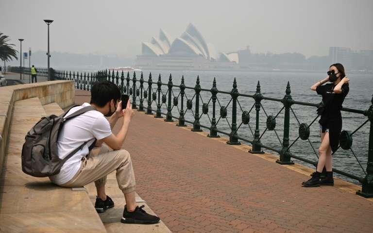 Des touristes portent des masques en raison des fumées toxiques liées aux incendies de forêts, le 10 décembre 2019 à Sydney, en Australie. © Peter Parks, AFP, Archives