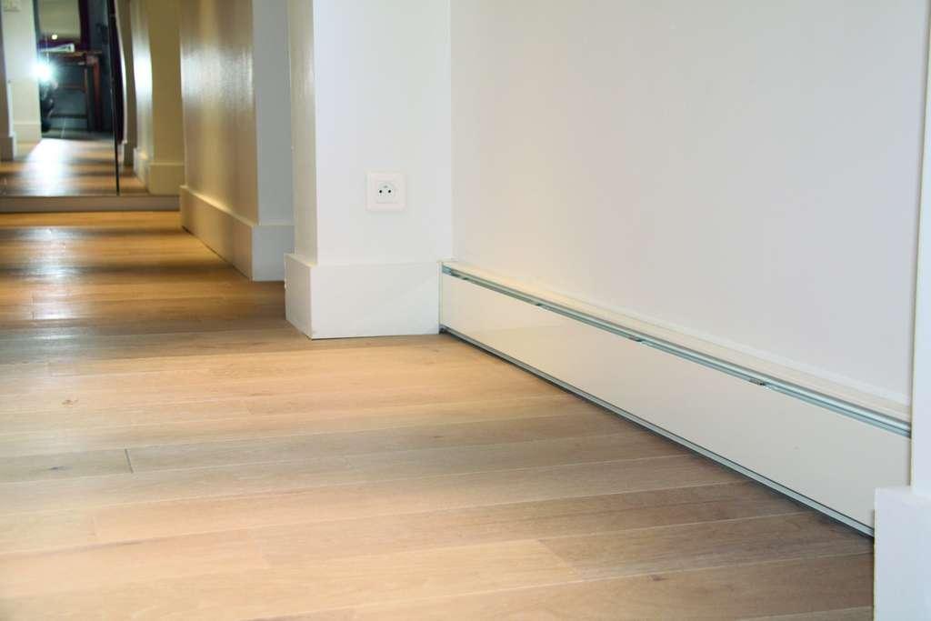 D'une épaisseur de 3 cm pour 15 cm de haut, les plinthes chauffantes sont particulièrement discrètes. Contrairement à un plancher chauffant en cas de problème, il est possible d'intervenir facilement pour réparer ou remplacer un élément. © Ecomatic