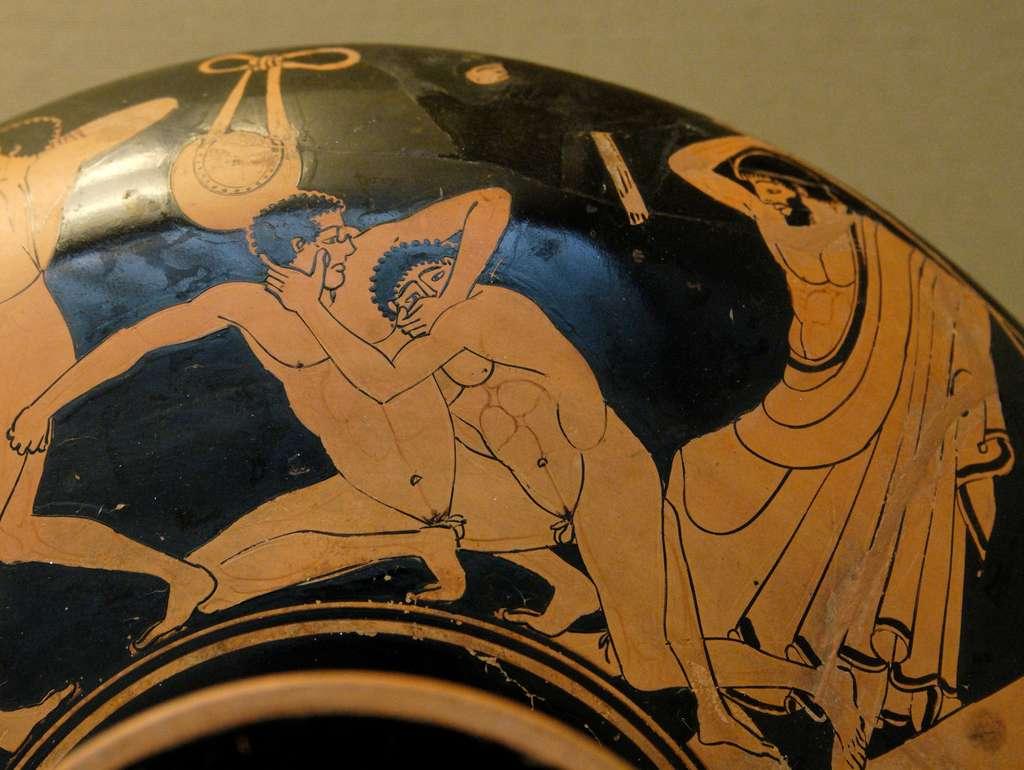 Scène de pancrace peinte sur un kylix. Le lutteur de droite essaie de crever l'œil de son adversaire. L'arbitre intervient avec un fouet pour sanctionner la faute. © Domaine public
