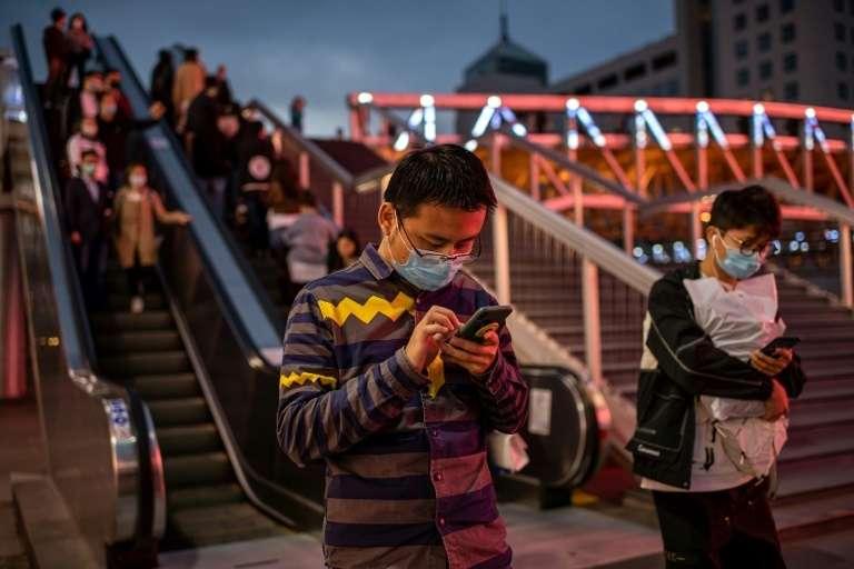 Des personnes consultent leurs smartphones à l'extérieur d'un centre commercial, le 11 octobre 2020 à Pékin. © Nicolas Asfouri, AFP
