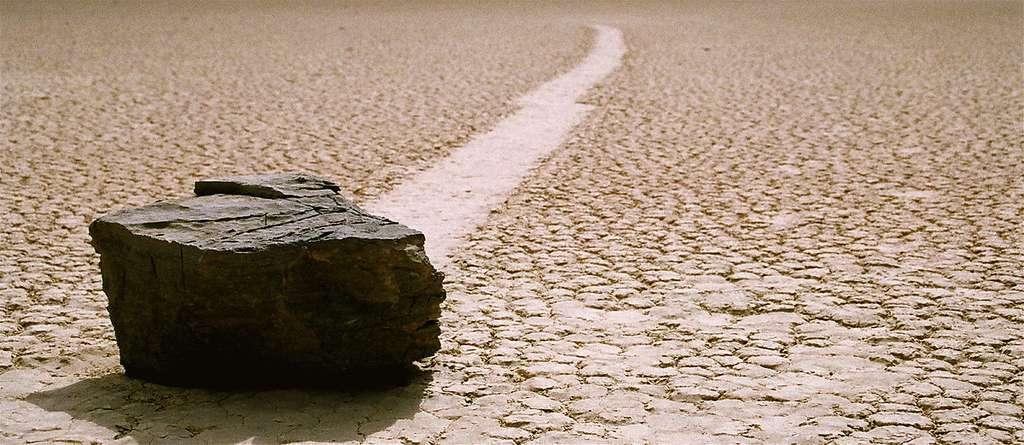 Un rocher et sa trace bien visible sur le site de Racetrack Playa, en Californie. Le mouvement ne suit pas la pente (très faible), mais la direction des vents dominants, sud ou sud-ouest. © Tahoenathan, cc by nc sa 3.0
