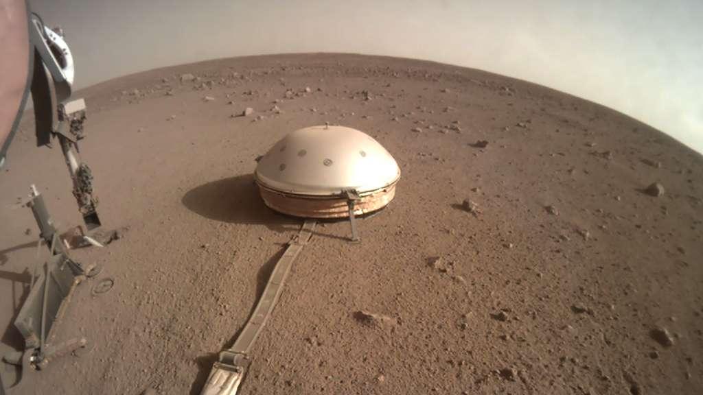 Le sismomètre Seis sur la surface de Mars. L'instrument est à l'abri sous son bouclier thermique et éolien. À gauche, on aperçoit l'instrument HP3 (Heat Flow and Physical Properties Package) qui n'est jamais parvenu à s'enfoncer dans le sol martien. © Nasa