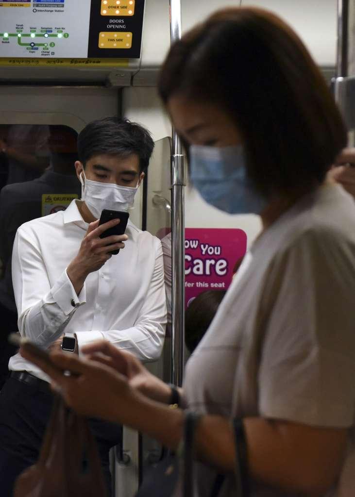 Des banlieusards portant des masques facial et regardent leurs téléphones portables dans le Métro du Singapour, le 18 mars 2020. © Catherine Lai, AFP