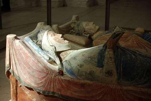 Le gisant couché en tuffeau polychrome d'Aliénor d'Aquitaine (avec Henri II au second plan), à l'abbaye de Fontevraud. Reine de France de 1137 à 1152, elle est représentée à une trentaine d'années, coiffée de la couronne royale avec pour la première fois, en Occident médiéval, le thème de la femme lectrice (lisant probablement un psautier). © Elanor Gamgee, Wikipédia, licence Creative Commons Paternité 3.0 (non transposée).