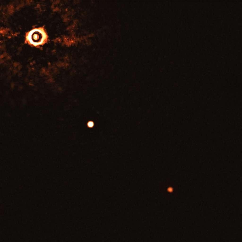 Sur cette image capturée par l'instrument Sphere du VLT de l'ESO figure l'étoile TYC 8998-760-1 entourée de deux exoplanètes géantes. C'est la toute première fois que les astronomes parviennent à observer directement plus d'une planète en orbite autour d'une étoile semblable au Soleil. Cette image a été acquise au moyen d'un coronographe. Ce dispositif permet de bloquer la lumière en provenance de la jeune étoile de type Soleil (située dans l'angle supérieur gauche), et donc de détecter la présence de planètes de luminosité moindre. Les anneaux brillants et foncés qui couvrent la surface de l'étoile sont des artéfacts optiques. Les deux planètes figurent sous l'aspect de deux points brillants situés l'un au centre, l'autre dans l'angle inférieur droit de l'image. © ESO, Bohn et al.