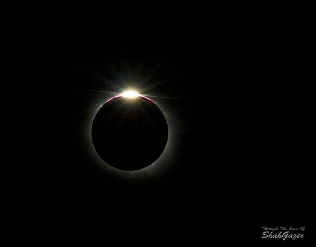Un dernier rayon de Soleil se glisse entre deux montagnes lunaires avant la phase totale de l'éclipse. Outre la couronne solaire blanche qui commence à devenir visible, on observe également des protubérances solaires roses. © Shahrin Ahmad