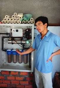Chai Lo, co-fondateur de l'ONG 1001 Fontaines, devant le « placard de filtration d'eau » qu'il installe dans des villages de l'ouest du Cambodge. © Lionel Goujon et Gwenael Prié