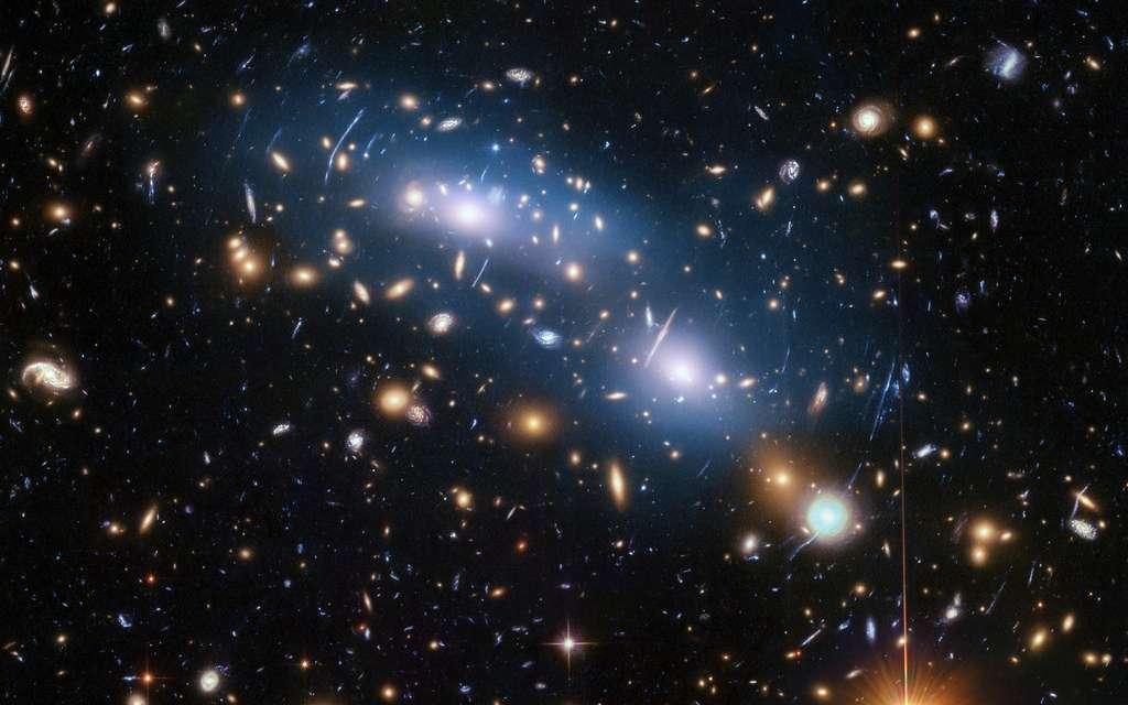 Cette image du télescope spatial Hubble de la Nasa/ESA montre l'amas de galaxies MACS J0416. Il s'agit de l'un des six amas étudiés par le programme Hubble Frontier Fields, qui a produit les images les plus profondes de lentilles gravitationnelles jamais réalisées. Les scientifiques ont utilisé la lumière intra-amas (visible en bleu) pour étudier la distribution de la matière noire au sein de l'amas. © Nasa, ESA et M. Montes (Université de New South Wales, Sydney, Australie)