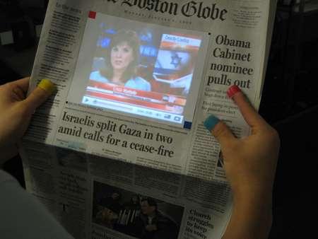 Utilisation de Sixth Sense pour projeter une vidéo venue du Web sur un magazine. © DR