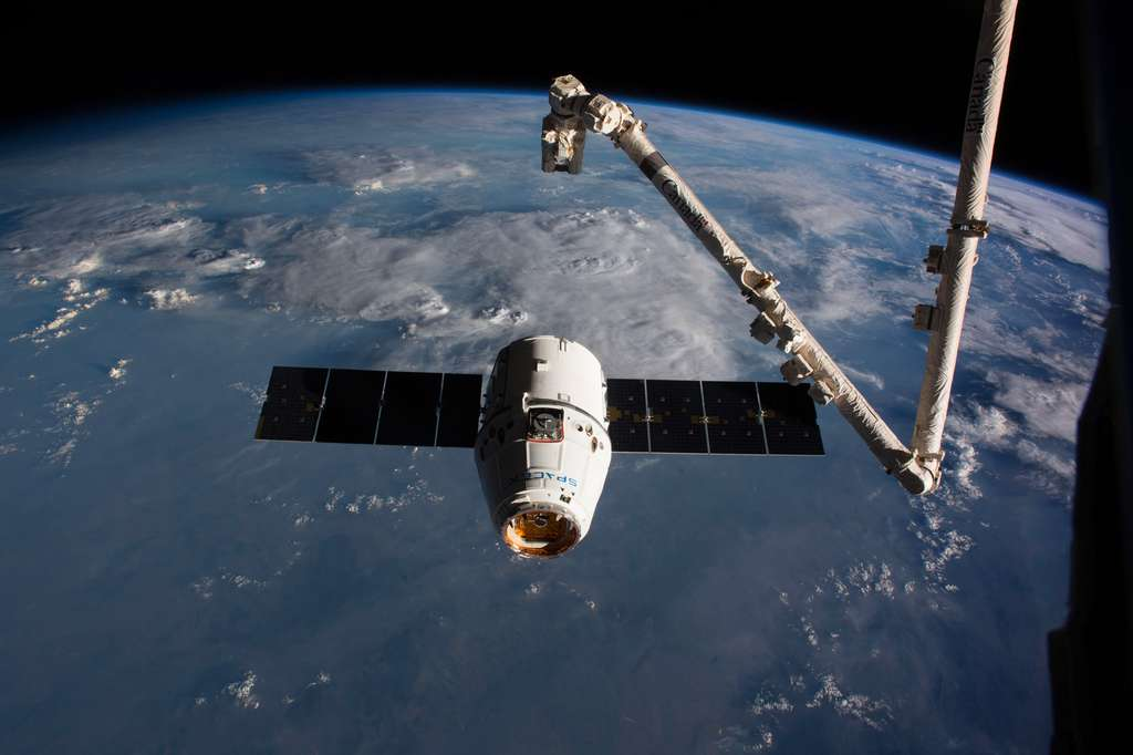 Une capsule Dragon s'apprête à se faire saisir par le bras robotique de la Station pour l'amarrer au complexe orbital. © Nasa