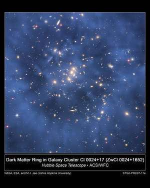 L'anneau de matière noire de l'amas de galaxies CL 0024+17. Il s'agit d'une carte de la matière noire réalisée à partir de la distorsion des rayons lumineux provenant des galaxies à l'arrière plan et surimposée à l'image prise initialement par Hubble (Crédit: NASA, ESA, M.J. Jee and H. Ford).