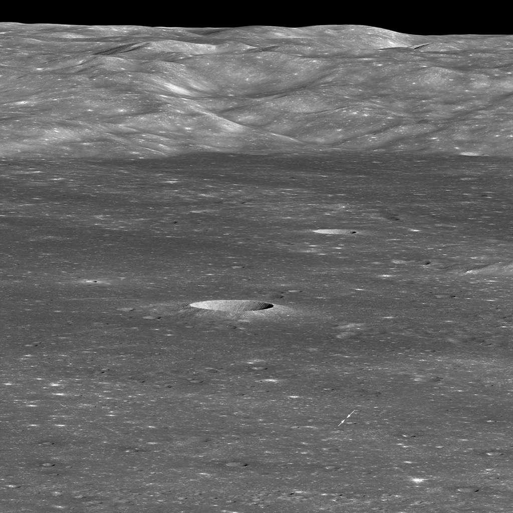 Le cratère von Kármán, terrain de jeu lunaire de la mission chinoise Chang'e 4, vu par la sonde spatiale américaine LRO en orbite autour de la Lune le 30 janvier 2019. L'atterrisseur est le tout petit point blanc indiqué par les deux flèches. Le rover Yutu 2 n'est pas visible. Les montagnes au loin forment la paroi occidentale du cratère von Kármán. Le petit cratère que l'on voit très clairement au milieu de l'image fait 3.900 m de diamètre et 600 m de profondeur. © Nasa/GSFC/Arizona State University