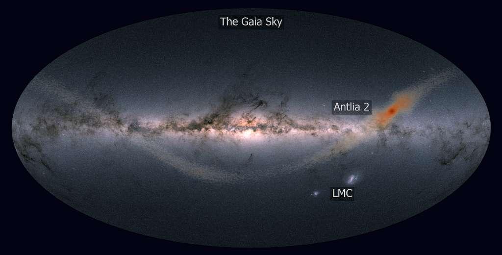 Antlia 2 est une géante parmi les galaxies naines car diffuse mais de faible masse. Alors qu'Antlia 2 est en orbite autour de la Voie lactée, ses étoiles sont arrachées par les forces de marée de la Voie lactée. Les étoiles orange montrent les résultats d'un modèle informatique d'Antlia 2 soumis à ces forces qui produisent donc une sorte de courant d'étoiles, dit courant de marée. L'arrière-plan montre la vue du satellite Gaia sur l'ensemble du ciel nocturne. Le Grand Nuage Magellan (LMC) est visible sous le disque de la Voie Lactée – bien que de taille similaire à Antlia 2, le LMC est 10.000 fois plus lumineux ! © J. Sanders (Cambridge, UK) based on the image by Gaia Data Processing and Analysis Consortium (DPAC)/A. Moitinho/A. F. Silva/M. Barros/C. Barata, Université de Lisbonne, Portugal /H. Savietto, Fork Research, Portugal