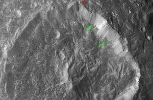 Des dépôts poussiéreux sombres sont visibles à la base des remparts du cratère Herschel (flèches vertes). La flèche rouge indique une bande de débris s'étant écoulés le long de la paroi. Crédit Nasa