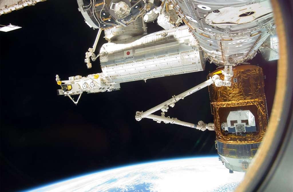 La partie japonaise de la Station spatiale internationale avec, au premier plan, le véhicule de fret HTV et le bras robotique canadien (Canadarm2). En arrière-plan le laboratoire scientifique Kibo, le bras robotique et la plateforme externe destinée à recevoir les instruments et expériences devant être exposés au vide spatial. © Nasa