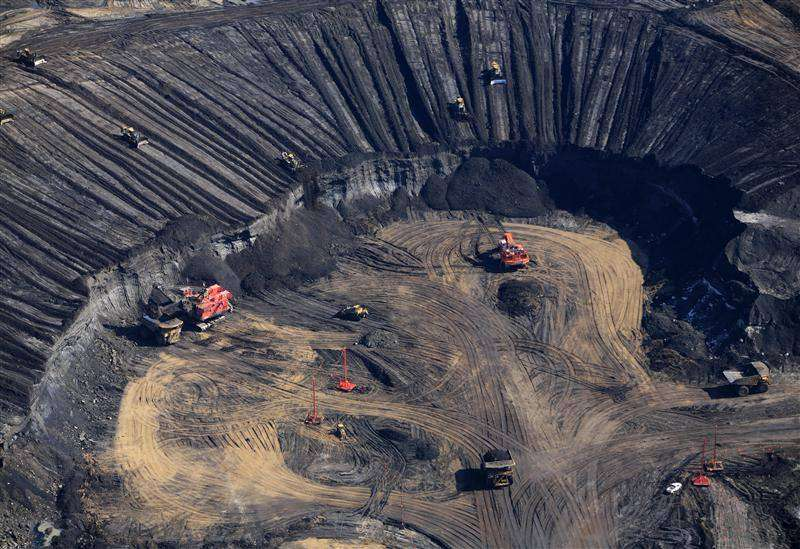 Les zones de sable bitumineux proches de la surface sont exploitées via des mines à ciel ouvert. Pour atteindre le sable, il faut retirer la couche superficielle de terre, qui sera stockée et réutilisée pour la réhabilitation du site. Des trous sont réalisés et les mottes prélevées sont mélangées à de l'eau pour être transportées par pipeline vers une usine où le bitume est séparé du sable. © Colin O'Connor, Greenpeace