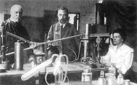 Marie Curie aux commandes, la main droite sur le poids de la balance à quartz, la main gauche sur le chronomètre et l'œil fixé sur la tache de lumière sur la règle. À ses côtés, Pierre Curie et son assistant, Petit. L'électromètre est ici en dehors de l'image, sur la gauche. ©ACJC
