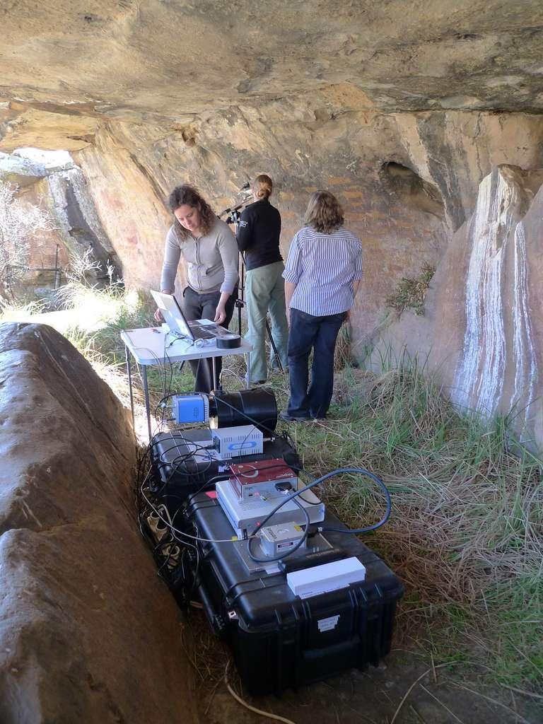 Le matériel est installé dans la grotte sur les caisses ayant servi au transport : le laser et son électronique de contrôle (boîtiers gris et rouge), le spectromètre (cylindre noir) et son détecteur CCD (boîtier bleue). L'ordinateur de pilotage est, lui, sur une table. Site BUF1, Eastern Cape, Afrique du Sud. © Luc Ronat/CNRS Photothèque