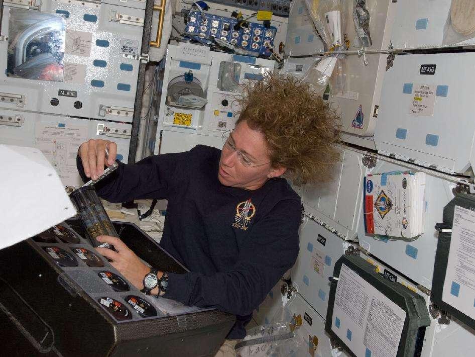 Sandy Magnus pendant les opérations de transfert de matériel entre l'ISS et la navette, dans un sens et dans l'autre puisque la navette peut redescendre du fret sur Terre, à la différence des autres engins existants, capsules russes, ATV européen ou HTV japonais. © Nasa
