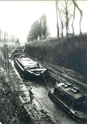 Scène de touage dans la tranchée d'Escommes, dans les années 30. Le toueur emmène un long convoi dont le premier bateau semble être un « gros numéro », bateau métallique livré par l'Allemagne en dommage de guerre. © DP