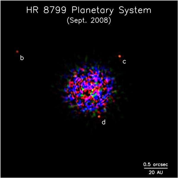 HR 8799 et ses trois exoplanètes vues par les instruments de Keck en 2008. L'image centrale de l'étoile a été soustraite par un processus de traitement de l'image pour faire apparaître les trois exoplanètes. La tache que l'on voit au centre est donc un artefact de ce traitement de l'image. © Keck Observatory
