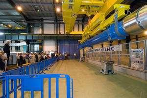 Le dernier aimant avant sa descente dans le tunnel, avec la banderole avant qu'elle ne soit modifiée. A gauche, Claude Hauviller, chef du groupe Coordination de l'installation du département TS, s'adresse aux invités venus assister à l'événement (Crédit : CERN).
