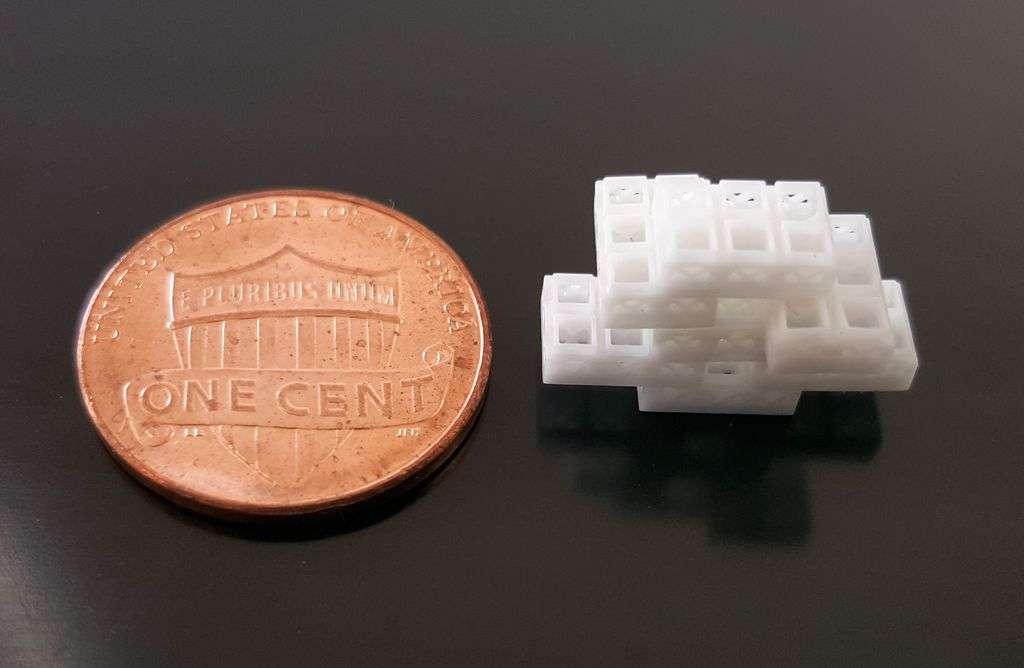 Plusieurs briques empilées comparées à une pièce de 1 centimes de dollar. © OHSU