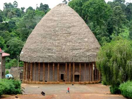 Grande case de Bandjoun, typique de l'architecture traditionnelle Bamiléké. Les murs sont en raphia noué, les piliers sont en bois sculpté, et le toit en chaume. Cette case est utilisée pour des événements traditionnels particuliers. © Olivier Testa