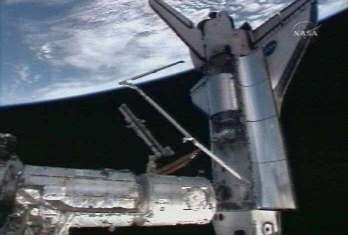 Extrait de la soute de la navette, le module Columbus va bientôt être fixé sur la Station spatiale internationale. © Nasa-TV