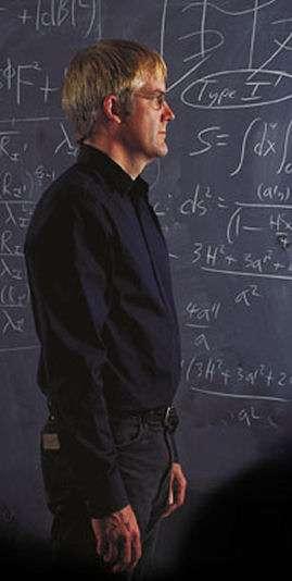 Joseph Lykken, un théoricien des cordes spécialisé dans la phénoménologie des particules élémentaires devant des calculs de cosmologie relativiste et de théorie des cordes. Crédit : Quantum Universe
