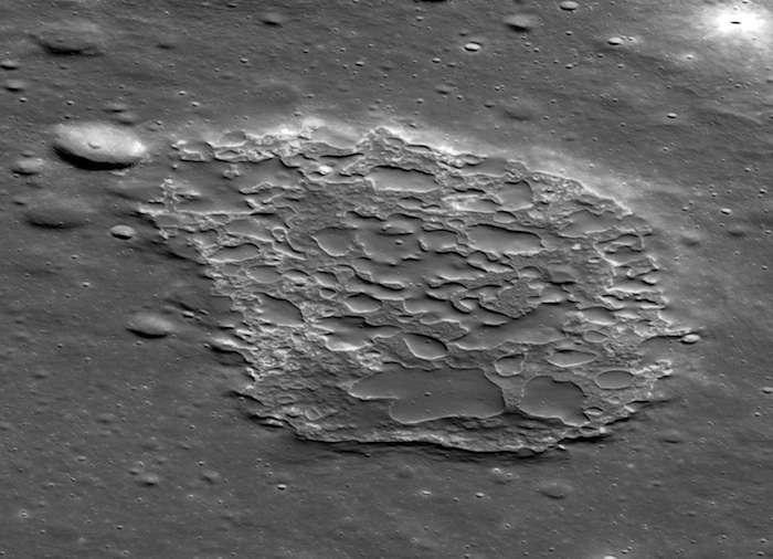 L'IMP Ina est large de 3 kilomètres et profonde et 50 mètres environ de profondeur. Son sol est recouvert de nombreux petits monticules de lave. Le nombre de cratères observés sur les monticules indique que les éruptions qui les ont formés ont eu lieu il y a environ 33 millions d'années. © NASA/GSFC/Arizona State University