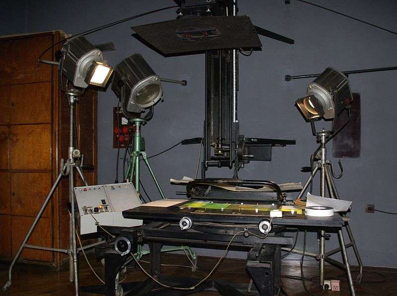 L'installation nécessaire pour filmer un dessin animé sur cellulo se présente ainsi. La caméra est située tout en haut de l'image. Elle peut descendre ou monter pour zoomer-dézoomer sur les cellulos, posés à plat sur la table. © Janericloebe, Wikimedia Commons, DP