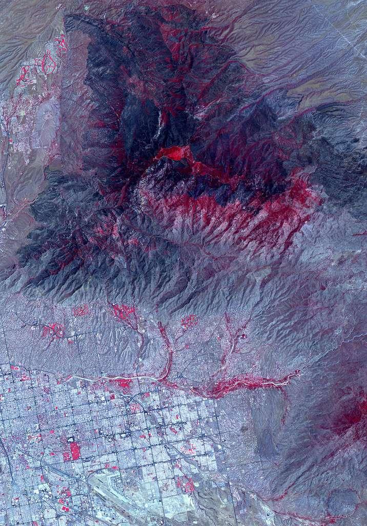 Sur cette image du radiomètre avancé d'émission et de réflexion thermiques spatiales (Aster) embarqué à bord du satellite Terra de la Nasa, les zones brûlées apparaissent en gris foncé et la végétation en rouge. © Nasa