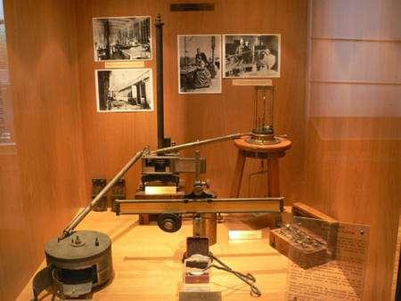 Le « montage Curie » de mesure de la radioactivité (exposé au musée Curie à Paris) : à gauche la « boîte » est la chambre d'ionisation où est placé l'échantillon dont on mesure l'activité, au centre (au fond) l'électromètre, au premier plan, la réglette graduée et, accrochée dessous la lampe dont la lumière est réfléchie par le miroir suspendu au fil de l'électromètre. À droite, au fond, la balance à quartz ajoutée ensuite, et sa boîte de poids.